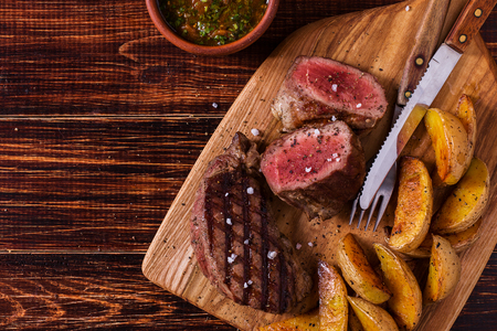salsa: Grilled steak with potato wedges, salsa and spices on dark wooden background. Stock Photo