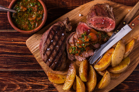 Grilled steak with potato wedges, salsa and spices on dark wooden background. Фото со стока