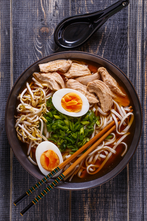 ramen: Japanese ramen soup with chicken, egg, chives and sprout on dark wooden background. Stock Photo
