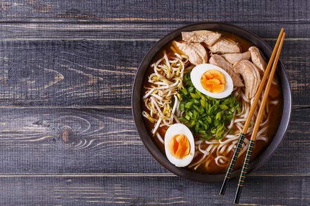 Japanese ramen soup with chicken, egg, chives and sprout on dark wooden background. Imagens