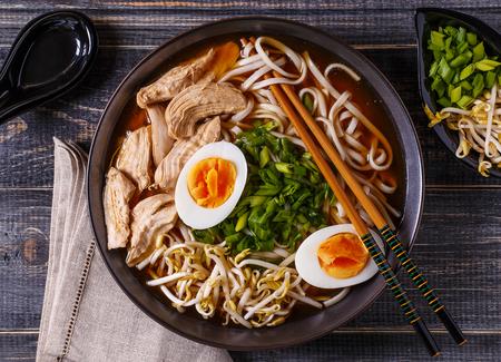 닭고기, 계란, 향신료와 어두운 나무 배경에 새싹 일본라면 스프.