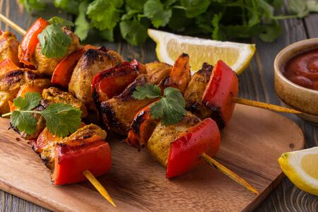 Grilled chicken and vegetable kebabs on dark background.