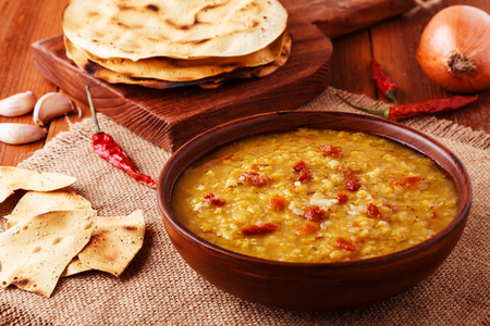 Thick indian red lentil soup with cilantro served with indian flat bread on a wooden background. 版權商用圖片 - 53701376