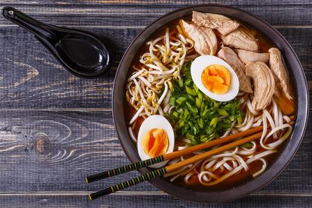 어두운 나무 배경에 닭고기, 계란, 향신료와 새싹 일본라면 수프.