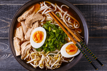 Japanese ramen soup with chicken, egg, chives and sprout on dark wooden background. Reklamní fotografie