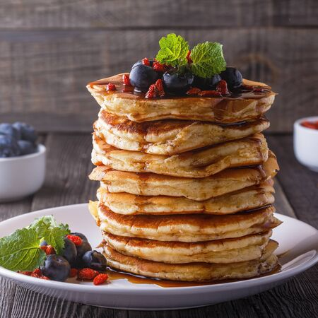 maple syrup: Stack of pancakes with fresh blueberry, goji berries and maple syrup.