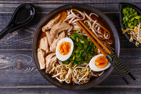 Japanese ramen soup with chicken, egg, chives and sprout on dark wooden background. Фото со стока