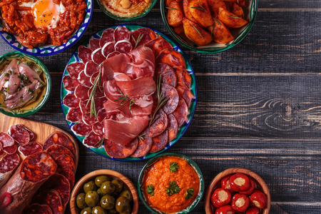 Typical spanish tapas concept. Concept include variety slices jamon, chorizo, salami, bowls with olives, peppers, anchovies, spicy potatoes, mashed chickpeas on a wooden table.