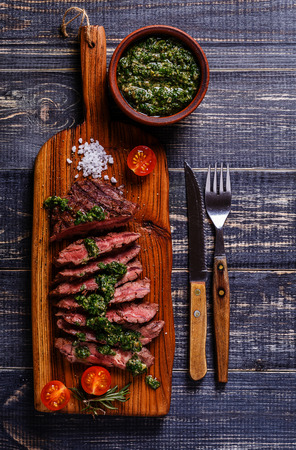 Steak served on a board with salsa verde, top view.