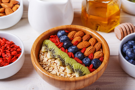 almond: Healthy breakfast - bowl of oat flakes with fresh fruit, almond and honey, selective focus.