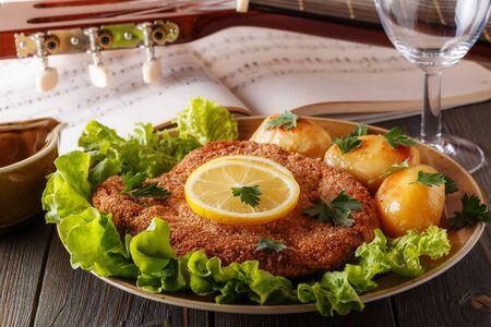 schnitzel: Wiener schnitzel with potatoes and salad, selective focus.