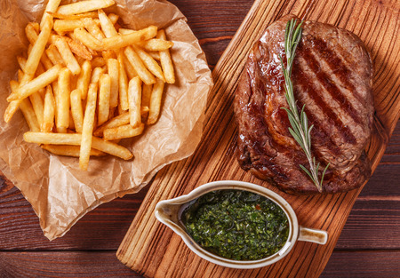 Beef barbecue ribeye steak with chimichurri sauce and french fries, top view. Фото со стока