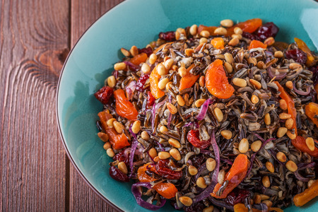 pine  fruit: Homemade salad with wild rice, dried fruit and pine nuts, selective focus.