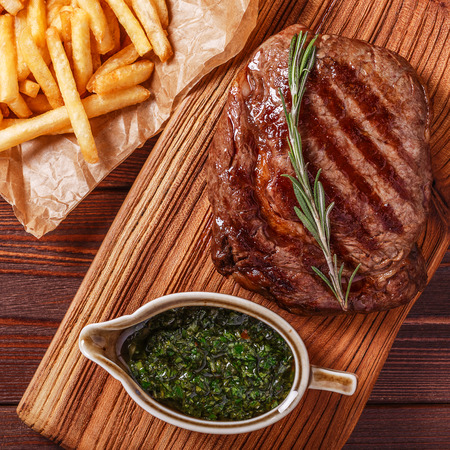 ribeye: Beef barbecue ribeye steak with chimichurri sauce and french fries, top view. Stock Photo