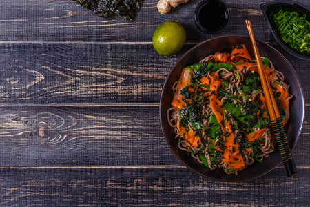 soba noodles: Soba noodles with vegetables and seaweed, top view.