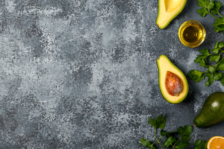 Food background with avocado, lemon, parsley and olive oil on concrete surface, top view, copy space.
