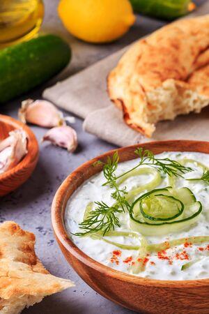 tzatziki: Greek salad tzatziki of cucumber, yogurt , olive oil, garlic, dill and spices, selective focus. Stock Photo
