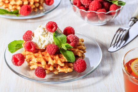 mascarpone: Waffles garnished with mascarpone and raspberries, selective focus.