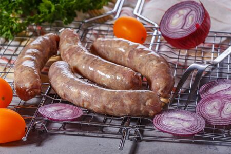 grate: Raw sausages with vegetables and spices on the grill grate. Stock Photo