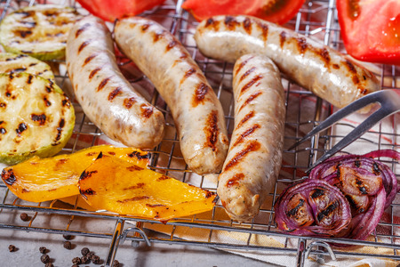 grate: Cooked sausages with vegetables and spices on the grill grate. Stock Photo