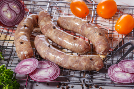 Raw sausages with vegetables and spices on the grill grate. Stock Photo