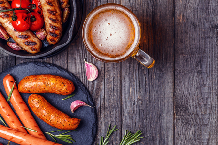 Grilled sausages with glass of beer on wooden table. Top view with copy space. Foto de archivo