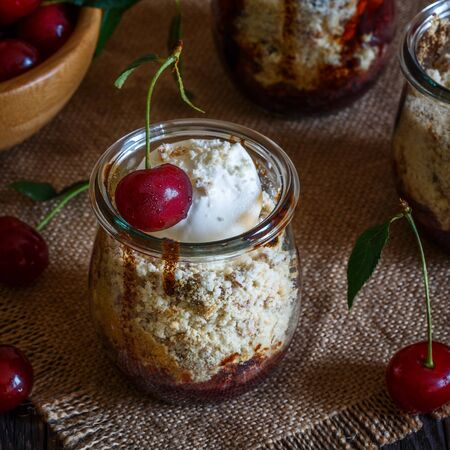 Homemade cherry crumble in glass jars on a dark wooden background, selective focus.