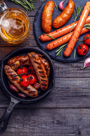 Grilled sausages with glass of beer on wooden table. Top view with copy space. Фото со стока
