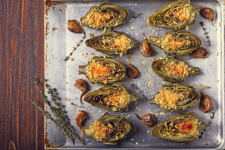 Artichokes baked with cheese, garlic and thyme on a baking sheet, top view. Stockfoto