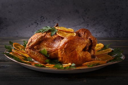 whole chicken: Homemade roasted whole chicken with parsley and oranges, selective focus.