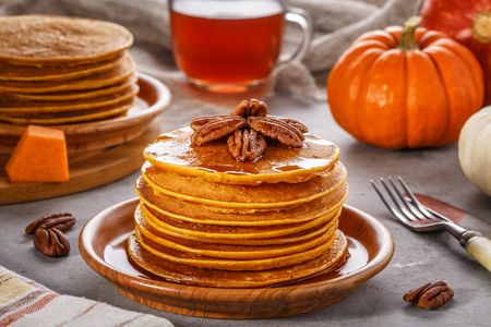 Stack of homemade pumpkin pancakes with pecans and maple syrup, selective focus. Stock Photo