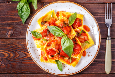 Ravioli with tomato sauce and basil on dark background, top view.