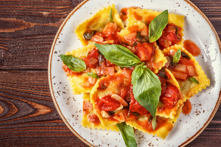 meat sauce: Ravioli with tomato sauce and basil on dark background, top view.