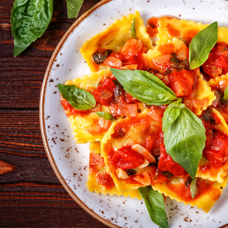 tortellini: Ravioli with tomato sauce and basil on dark background, top view.