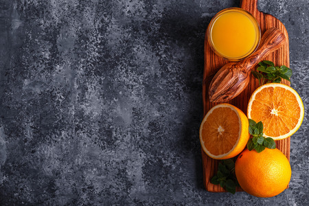 Fresh ripe oranges and juice on stone table, top view, copy space. Stock Photo