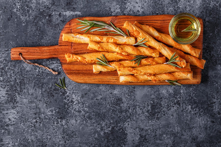 grissini: Grissini bread sticks on wooden cutting board  over concrete textured surface. Top view, copy space. Stock Photo