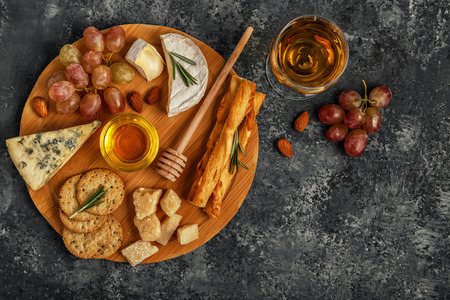 Assortment of cheese with wine, honey, nuts and grape on a cutting board, top view.