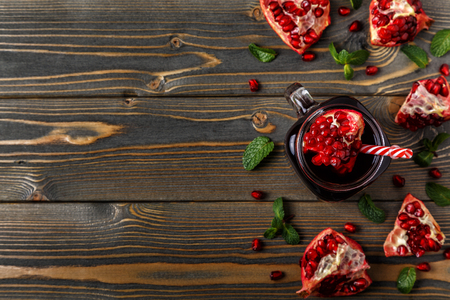 Glass of pomegranate juice with fresh pomegranate fruits and mint on wooden table, healthy drink concept.