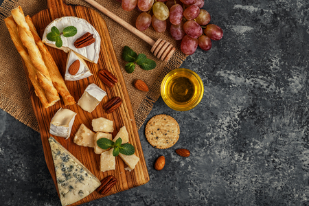 Assortment of cheese with honey, nuts and grape on a cutting board, top view.