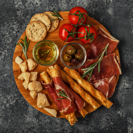 antipasto platter: Cheese and meat appetizer selection. Prosciutto, parmesan, bread sticks, olives, tomatoes on wooden board, top view.