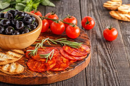 Spanish traditional chorizo sausage with fresh herbs, olives, tomatoes on a wooden board.