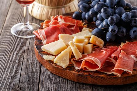 Prosciutto, wine, grape, parmesan on wooden table selective focus