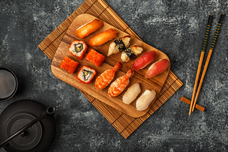 Sushi Set: sushi and sushi rolls on wooden plate, top view.