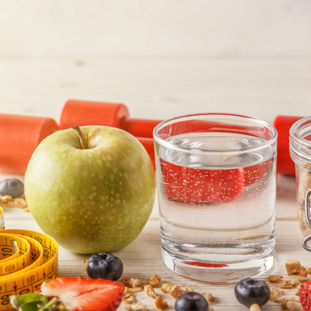Healthy breakfast, dumbbells and measuring tape on wooden background, selective focus. Stock Photo