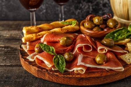 gressins: Prosciutto, craquelins, bâtonnets de pain avec du vin rouge, mise au point sélective.