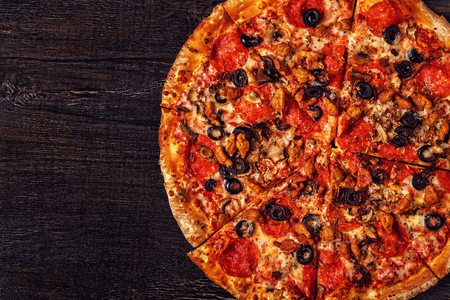 Pizza with mozzarella cheese, pepperoni, minced meat, ham, mushrooms, sweet green pepper, onion, black olives, top view. Stock Photo