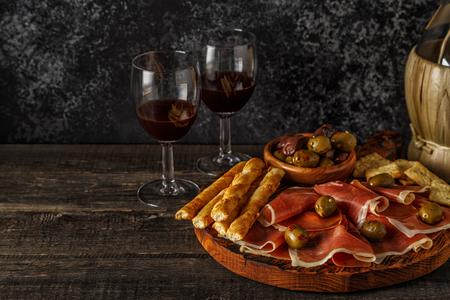 gressins: Prosciutto, cracker, bread sticks with red wine, selective focus.