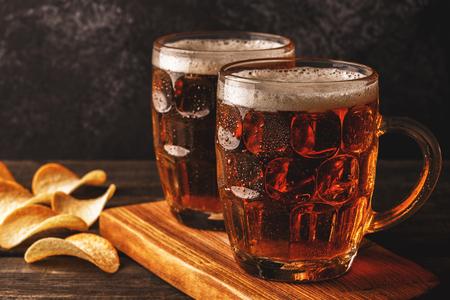 Bier. Koud bier in glas met chips op een donkere achtergrond.