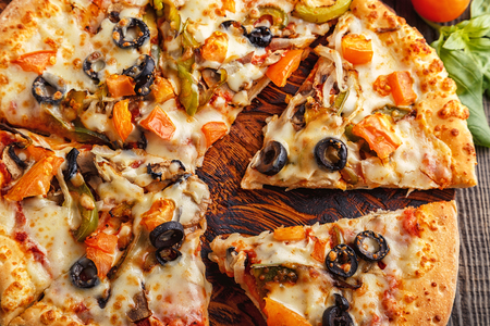 Vegetarian pizza with mozzarella cheese, tomatoes, champignons, onion, sweet green pepper, black olives, selective focus.
