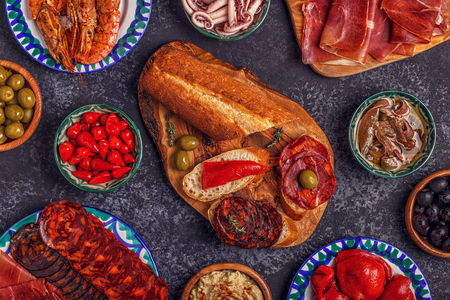 Typical Spanish concept of tapas. The concept includes a variety of pieces of jamon, chorizo, salami, bowls with olives, peppers, shrimps, anchovies, chickpeas puree.